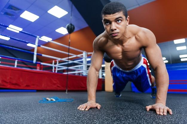 ボクシングのリングの近くで腕立て伏せをしているボクサー