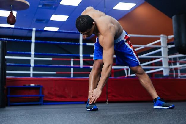 ボクシングのリングの近くでウォームアップ運動をしているボクサー