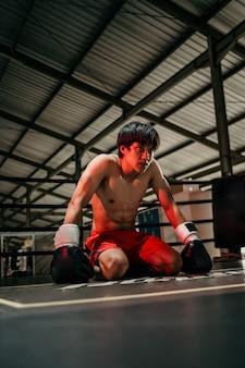 권투 장갑에 권투 선수는 반지의 바닥에 앉아