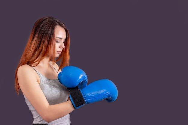 Девушка-боксер в синих боксерских перчатках в серой футболке в стойке на сером фоне copyspace