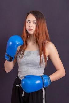 Боксер девушка в синих боксерских перчатках в серой футболке в стойке