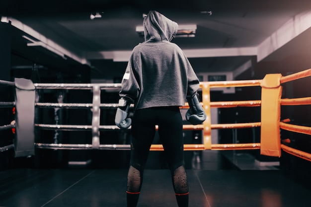 Boxer girl with hoodie and boxing gloves on standing in ring with backs turned.