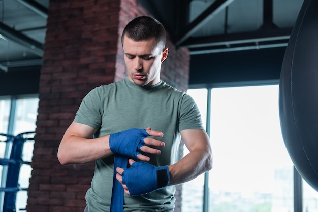 Boxer in gym. dark-haired promising skillful boxer using blue wrist wraps in light modern gym