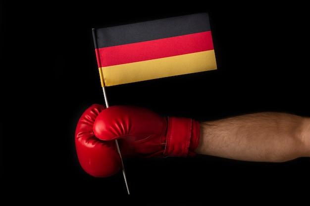 ボクサーの手はドイツの旗を握っています。ドイツ国旗のボクシンググローブ。黒い壁。