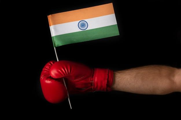 ボクサーの手は、インドの旗を持っています。インド国旗の付いたボクシング グローブ。黒い表面。