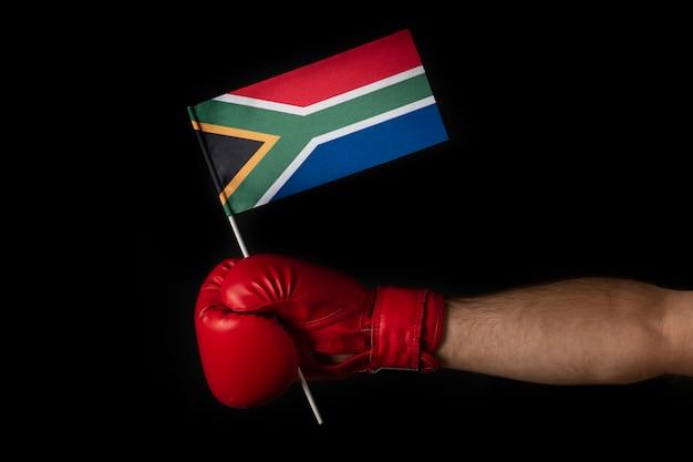 ボクサーの手は南アフリカの旗を握っています。南アフリカの旗が付いているボクシンググローブ。黒の背景。