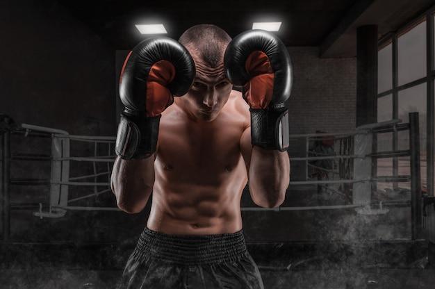 Боксер в тренажерном зале. он прикрывает голову перчатками. защитная стойка. смешанные боевые искусства. спортивная концепция.