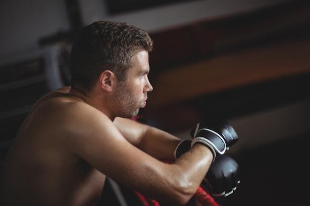 ボクシングのリングにもたれてボクサー