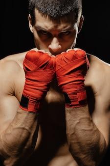 Боксер мужского пола, позирует в уверенной оборонительной позиции с руками в бинтах