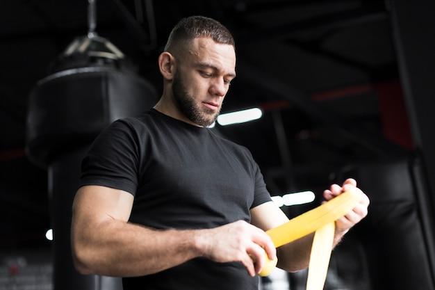 Боксер мужчина держит эластичный шнур