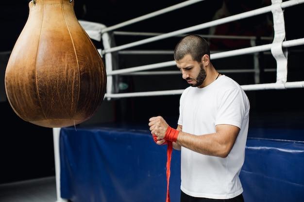 Боксер готовится к бою. молодой боксер в белой футболке. фото высокого качества