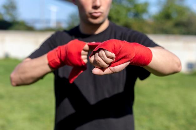 屋外で前腕包帯を使ってトレーニングの準備をしているボクサー