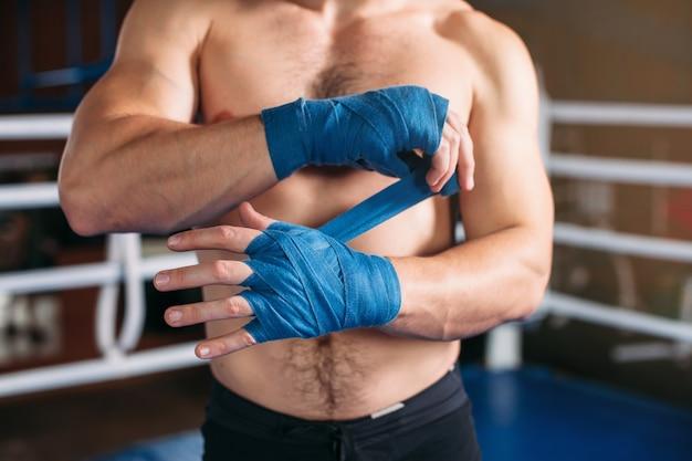 Боксер натягивает повязку перед боем или тренировкой.