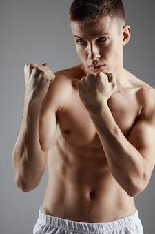 ボクサーは、筋肉の拳の灰色の背景のトレーニングをポンプアップ