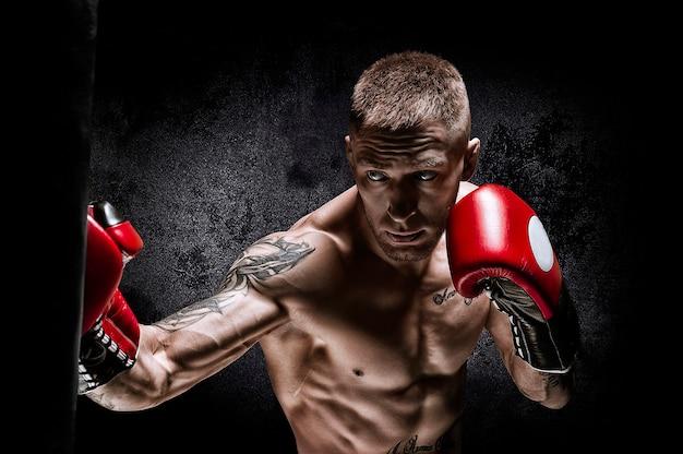 Боксер пробивает мешок. тренировка профессионального спортсмена. понятие о мма, борьбе, боксе. смешанная техника