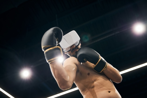 Boxer putting a block while covering his eyes with virtual reality glasses