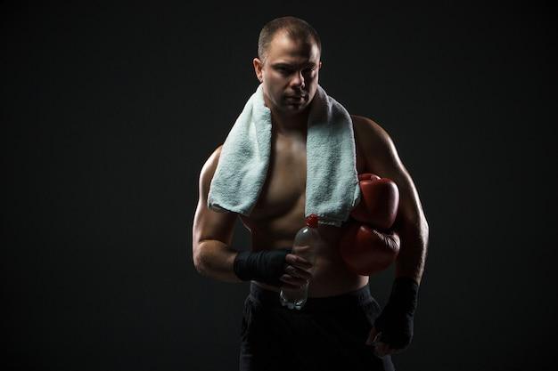 Боксер отдыхает с водой и полотенцем после тренировки