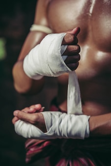 The boxer sat on the stone, tied the tape around his hand, preparing to fight.