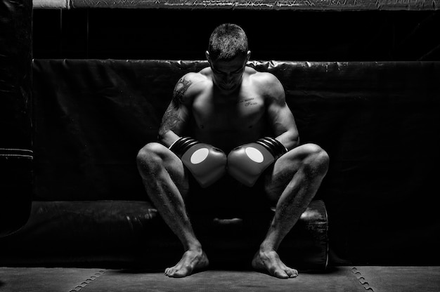 ボクサーは頭を下げて指輪の近くの手袋に座っています。スポーツ、ボクシング、総合格闘技、スポーツベッティングの概念。ミクストメディア
