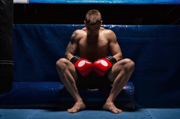 Боксер сидит в перчатках возле ринга, склонив голову. понятие о спорте, боксе, смешанных единоборствах, ставках на спорт. смешанная техника