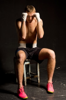 Boxer sitting on a stool in his corner of the ring in shadowed darkness