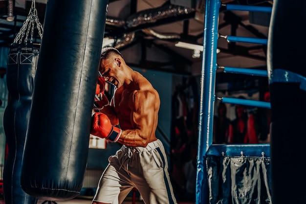 Тренировка боксера на боксерской груши в тренажерном зале
