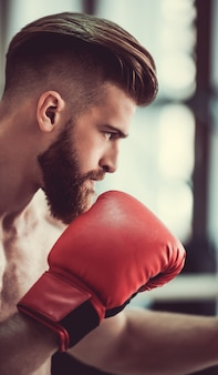 Boxer with bare torso in red boxing gloves ready to fight.