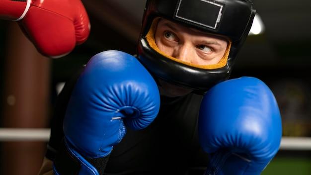 Боксер в шлеме и перчатках тренировки на ринге