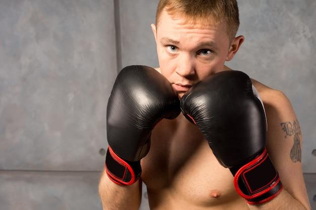 手袋をはめた拳を防御的に上げたボクサー