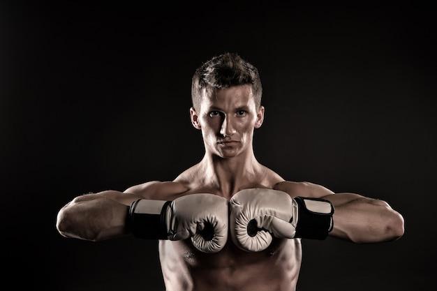 Боксер с сильными руками готов к бою. спортсмен человека с боксерскими перчатками на темном фоне. спорт, бокс, фитнес. сила, действие, энергия, активность. здоровье, благополучие, уход за телом, винтаж, нокаут