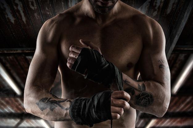 문신과 근육을 가진 복서가 테이프를 손에 붙입니다.