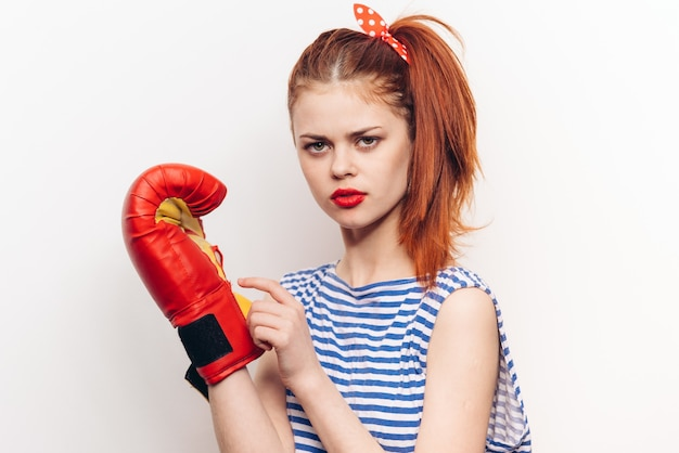 Boxer woman in red boxing gloves and a striped t-shirt on a light background
