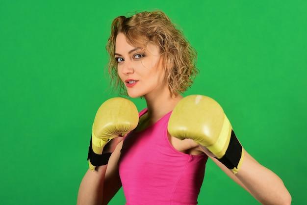 ボクサーの女性。スポーツのライフスタイル、パワー、アクティビティ、健康の概念-トレーニング前にボクシンググローブを着用したファイターボクサーの女の子。スポーツマンシップと強い体。ボクシング中の性的な女の子。アドバタイズ用のスペースをコピーします。