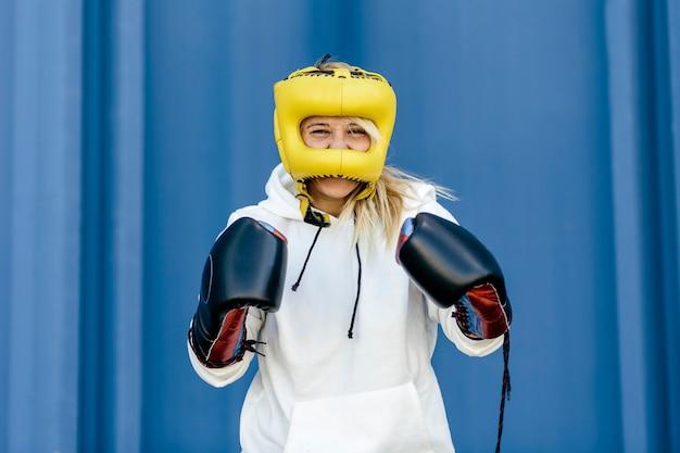 黄色のヘッドギアと黒い手袋を着用し、青い背景でカメラを見ているボクサーの女性。女性のボクサー、スポーツと自己改善の概念。コピースペースのある画像。