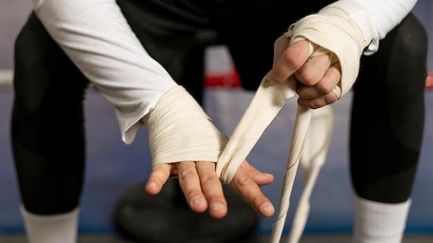 リングでトレーニングする前に手を包むボクサー