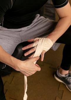 トレーニング前に手を包むボクサー