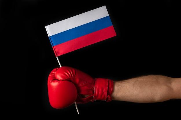 Рука боксеров держит флаг россии. боксерская перчатка с российским флагом. изолированные на черном фоне.