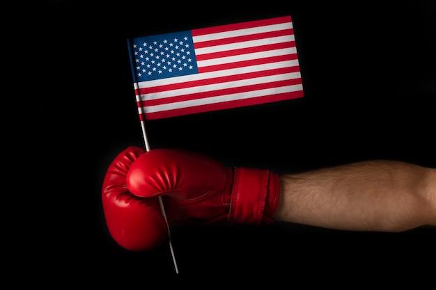 ボクサーの手は米国旗を保持しています。アメリカ合衆国の旗が付いているボクシンググローブ。黒の背景に分離。