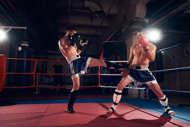 Боксеры тренируют кикбоксинг на ринге