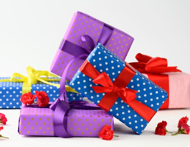 Boxes are packed in holiday paper with polka dots and tied with a silk ribbon on a background, birthday gift, surprise, close up