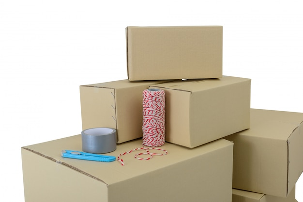 Boxes in different sizes stacked boxes, adhesive tape, rope and cutter isolated