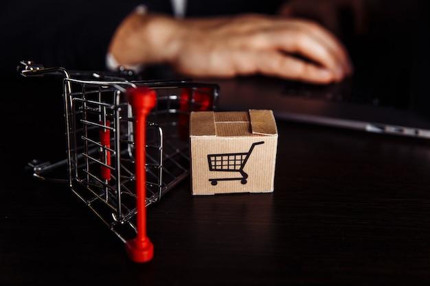 Ящики в тележке рядом с ноутбуком. концепция покупок в интернете