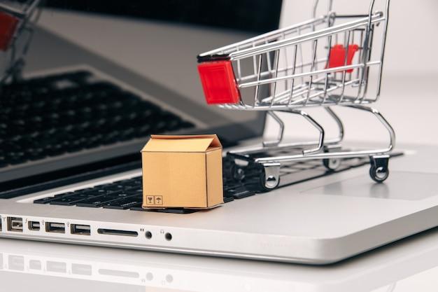 Коробки и тележка на ноутбуке. покупки в интернете - это форма электронной торговли, которая позволяет потребителям напрямую покупать товары у продавца.