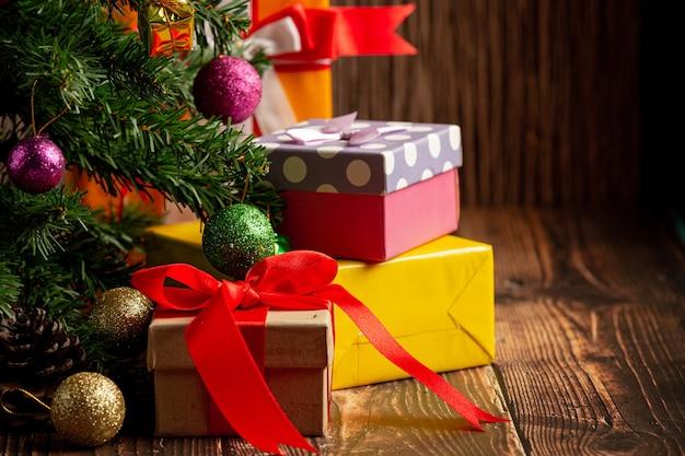 木製の背景にクリスマスの飾りとプレゼントの箱