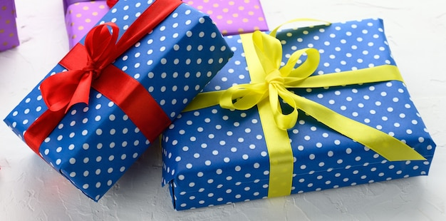 Boxes packed in festive blue paper and tied with silk ribbon on white background, birthday gift, surprise, close up Premium Photo