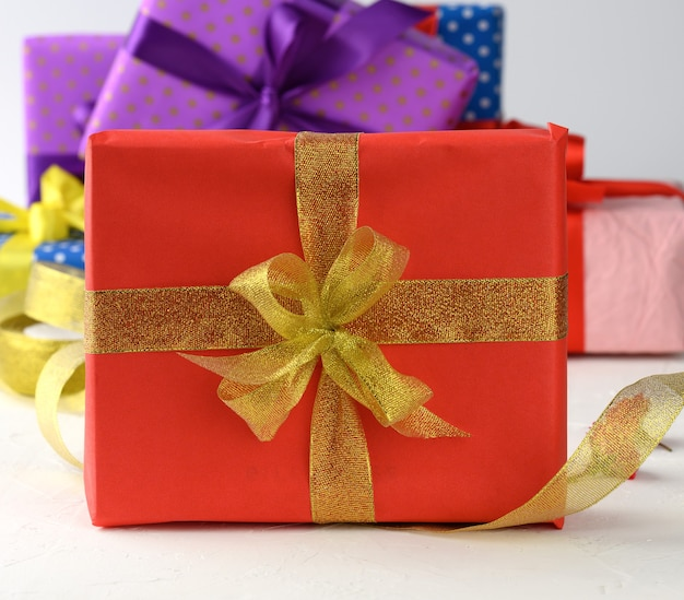 Boxes packed in festive paper and tied with silk ribbon on a white background, birthday gift, surprise
