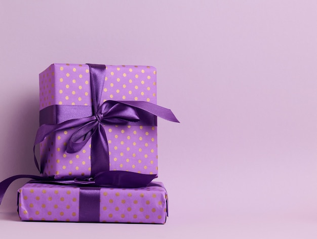 Boxes packed in festive purple paper and tied with silk ribbon on a purple background, birthday gift, surprise