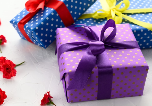 Boxes packed in festive purple paper and tied with silk ribbon on white background, birthday gift, surprise