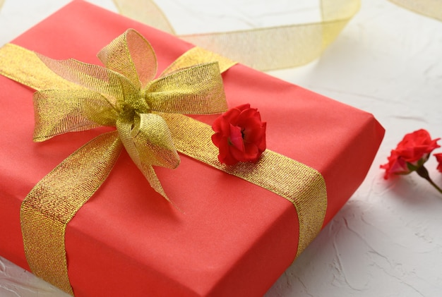 Boxes packed in festive red paper and tied with silk ribbon on white background, birthday gift, surprise, close up