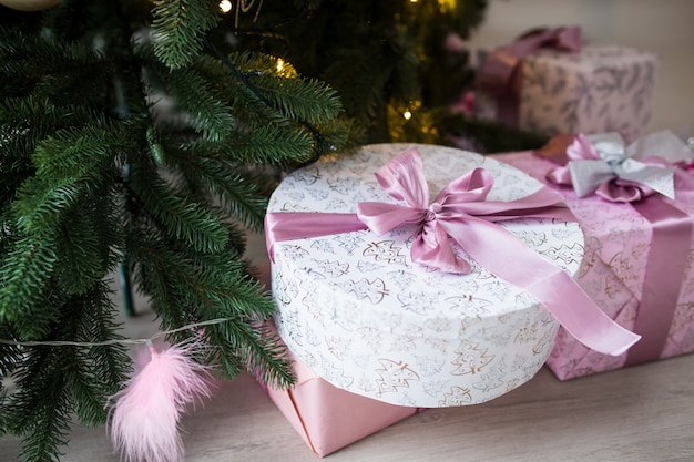 Boxes of pink color with gifts under a christmas tree. daylight bright light.